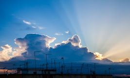 Sunbeams among the clouds over the antennae of the city. Sunbeams among the clouds over the antennae on the roofs of the city stock images