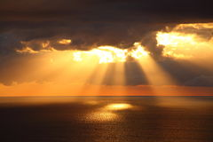 Sunbeams through dark clouds over ocean by golden sunrise