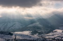 Sunbeams through clouds over the snowy mountains Royalty Free Stock Photo