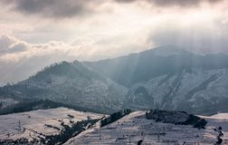 Sunbeams through clouds over the snowy mountains Royalty Free Stock Photos