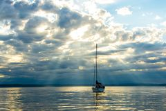 Sailboat emkpuomg Sunbeams. Sunbeams coming through clouds on Puget Sound Stock Photo
