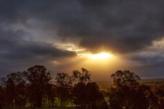 Sunbeams through dark clouds over mountain royalty free stock image