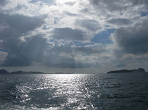 Sunbeams through dark clouds on sea Royalty Free Stock Image
