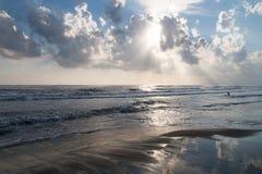 Sunbeams filtrują przez chmur na szorstkim morzu i plaży Fotografia Stock