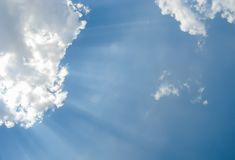 Sunbeams through fluffy white clouds in a blue sky Royalty Free Stock Image