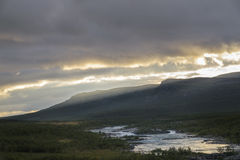 Sunbeams forming over mountains on sunset giving beautiful golden light over river in Sarek, Sweden Royalty Free Stock Images