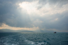 Sunbeams through hole in the clouds above ocean and ship Royalty Free Stock Photo