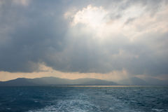 Sunbeams through hole in the clouds above ocean Stock Photo