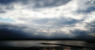 Sunbeams through moody clouds over water time-lapse stock video