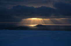 Sunbeams onto Sea Ice. Sunbeams shining down onto the sea ice and islands of the Windmill Islands near the Antarctic research base Casey stock photo