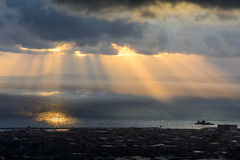Sunbeams over the city. Sun cuts through the clouds over the sea. And city Stock Photos