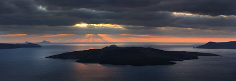 Sunbeams over Santorini volcano. Panorama. Sunbeams over Santorini volcano and steel surface of Aegean sea. Panorama Royalty Free Stock Images