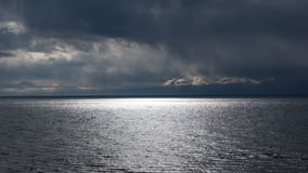 Sunbeams over the water in the rain Stock Image