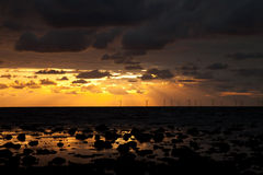 Sunbeams over a windfarm Stock Images