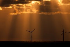Sunbeams over a windfarm Royalty Free Stock Photo