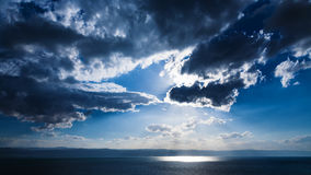 Sunbeams passes through dark clouds over Dead Sea Royalty Free Stock Image