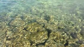 Sunbeams playing on the stones through the clear transparent water