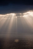 Sunbeams after rain. Over the sea Stock Images