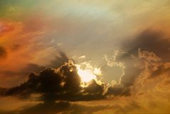 Sunbeams shine through gloomy clouds and color the sky in breathtaking colors. Sunbeams shine through gloomy clouds and color the sky in dark, breathtaking Stock Photo
