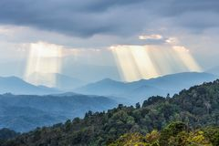 Sunbeams shining through cloudy sky to blue mountains Royalty Free Stock Photography