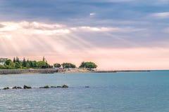 Sunbeams or sun rays at a sunrise on a beach in Sunny Beach on the Black Sea coast of Bulgaria. Crepuscular bulgarian clouds coastline dawn day god horizontal stock photography