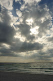 Sunbeams Trough the Clouds on a Sandy Beach Stock Photo