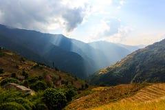 Sunbeams zaświeca przez chmura ryż poly na tarasach w himalaje, Nepal wiejskiego kszta?tuje powierzchni? fotografia royalty free