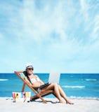 sunbed工作的性感的女孩与在海滩的一台膝上型计算机 免版税图库摄影