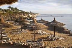 Sunbed, зонтик соломы на пляже захода солнца Стоковое Изображение
