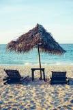 Sunbed и зонтик солнца nipa на пляже с белым песком во время захода солнца Стоковая Фотография