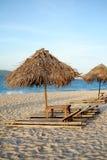 Sunbed и зонтик солнца nipa на пляже с белым песком во время захода солнца Стоковая Фотография RF