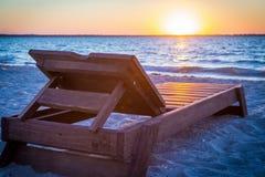 Sunbed на пляже на заходе солнца Стоковое фото RF