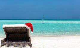 Sunbed с шляпой рождества на тропическом пляже Стоковые Фотографии RF