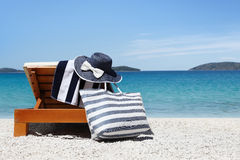 Sunbed with bag, blue hat and towel in the beach Stock Photo