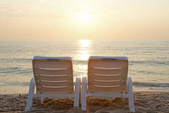 Sunbed on the beach. With beautiful sunrise background Royalty Free Stock Images