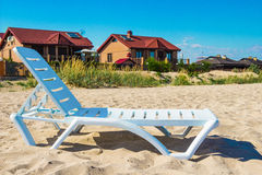 Sunbed on the beach. And houses with red roofs Stock Photos
