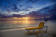 Sunbed on the beach at sunrise. Yellow sunbed on a beach at the waters edge with the sun rising over the sea in tha background Royalty Free Stock Photography
