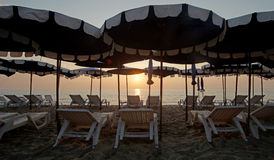 Sunbed and beach umbrella on the beach. With beautiful sunrise background Royalty Free Stock Photos