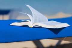 Sunbed with bed on the beach. Sunbed with opened book on the beach Stock Photo