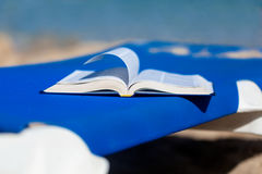 Sunbed with bed on the beach. Sunbed with opened book on the beach Stock Image