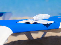 Sunbed with bed on the beach. Sunbed with opened book on the beach Stock Images