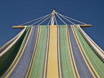 Sunbed and Blue Sky. Striped hammock watching the blue sky during a summer day Stock Photos