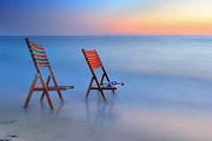 Sunbed or chair at the sea. Two chairs or sunbeds at the sea in the dusk or sunset long time exposure calmness  concept Royalty Free Stock Photography
