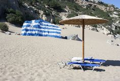 Sunbed and greek flag. Painted on rock stock images