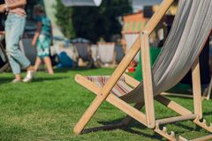Sunbed on green park with relaxing people. Garden lounge for sunbathing and rest Royalty Free Stock Photo