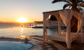 Sunbed and infinity pool at sunset. In Mykonos Royalty Free Stock Photo
