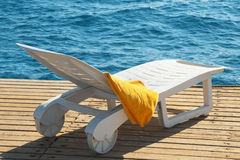 Sunbed near the sea. With a yellow towel Stock Images