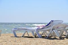 Sunbed near sea on sand Stock Photos