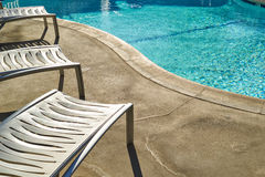 Sunbed near swimming pool in tropical resort Stock Image