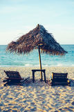 Sunbed and nipa sun umbrella on the white sand beach during sunset.  Stock Photography